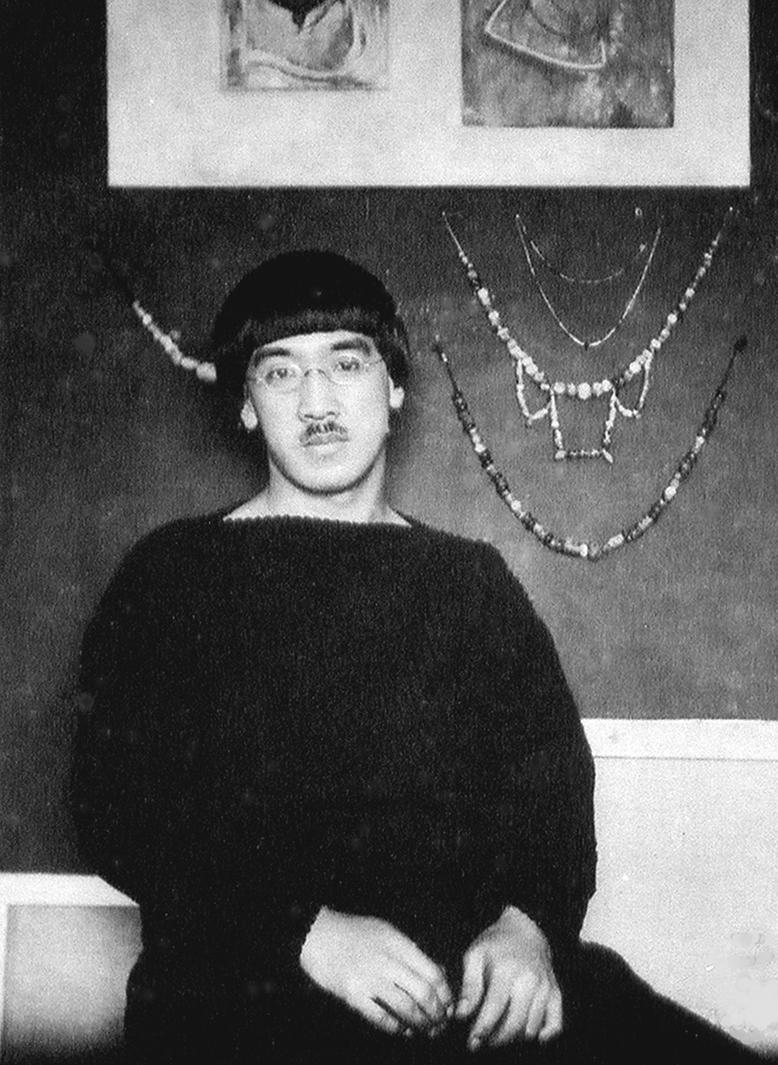 Paris, 1914-Tsuguharu Foujita, peu après son arrivée à Paris, posant devant des peintures réalisées d'après des oeuvres du Fayoum observées au Louvre et des colliers de sa composition, dans le premier atelier qu'il partage avec Kawashima Riichiro, à Montparnasse © Archives artistiques