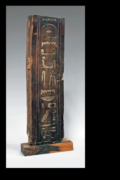 PLANCHE HIÉROGLYPHIQUE gravée dans le creux, en registre vertical, d'inscriptions entre deux bandes parallèles. Bois de cèdre.
