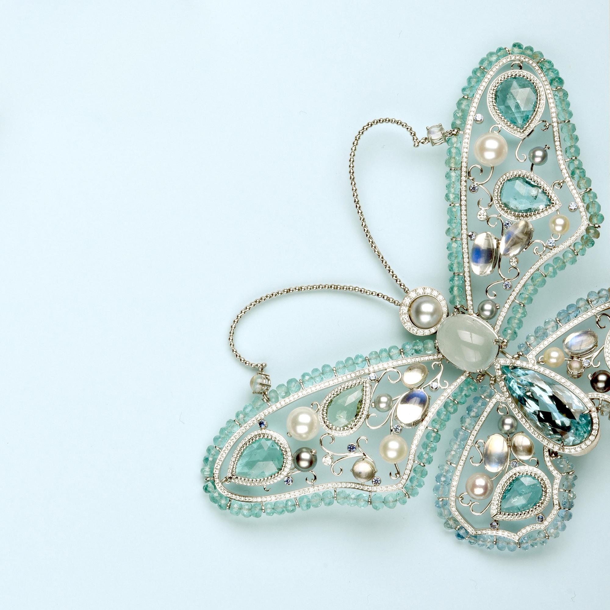 Clip en or blanc 750 signé «Chopard», pièce unique. Il stylise un papillon aux ailes déployées fait d'aigue-marine, perle de culture, brillants, tourmalines, pierres de lune. Hauteur env. 10cm, largeur env. 14cm, poids brut env. 71,8 g.